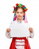 stock photo of national costume  - happy little girl in the Ukrainian national costume holding a sheet of paper with the space for text - JPG
