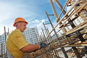 picture of concrete pouring  - builder worker knitting metal rods bars into framework reinforcement for concrete pouring at construction site - JPG