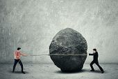 stock photo of irs  - Businessmen trying to move a huge stone - JPG