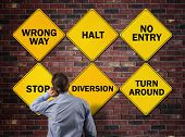 pic of no entry  - Businessman going the wrong way in front of a brick wall with stop - JPG
