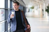 Businessman drinking coffee walking in airport. Casual urban professional smiling happy wearing suit