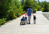 picture of father time  - A father spends time bonding with his two children while on a pleasure stroll along the boardwalk - JPG