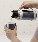 stock photo of thermos  - Pouring hot tea from thermos into cup - JPG