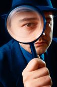 image of private detective  - Young man holding a magnifying glass up to his eye - JPG