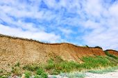 picture of geologie  - Earthen near to the sea with the blue sky with clouds - JPG
