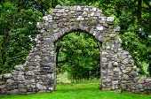 foto of old stone fence  - Old stone entrance wall in green landscaped garden - JPG