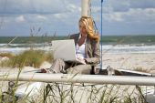 image of sail-boats  - A beautiful young woman in a smart suit sitting barefoot on the deck of a small catamaran sailing boat using her laptop computer with the beach and sea behind her - JPG