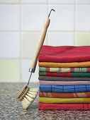Stack of kitchen towels with dish-washing brush