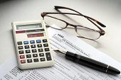 foto of cpa  - Tax preparation with fountain pen, calculator, glasses and forms