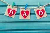 stock photo of wood craft  - Fathers day message on felt hearts over blue wooden board - JPG