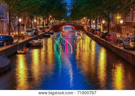 Night City View Of Amsterdam Canal And Luminous Track From The Boat