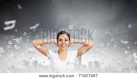 Young woman closing her ears with palms and enjoying the silence