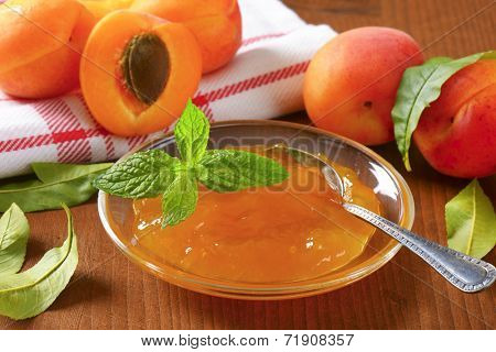 ripe apricots and bowl of apricot jam on wooden table