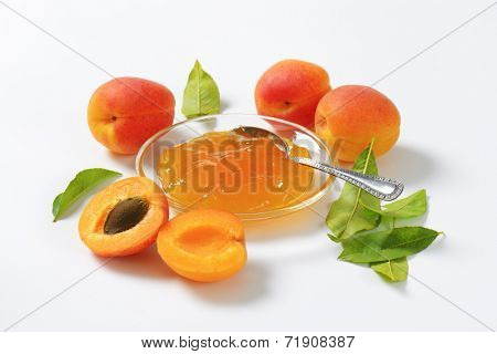 ripe apricots and bowl of apricot jam on white background