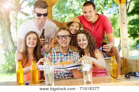 Friends drinking and eating pizza