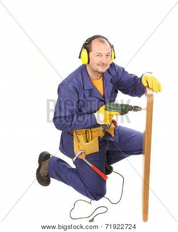 Worker in ear muffs with drill and board.