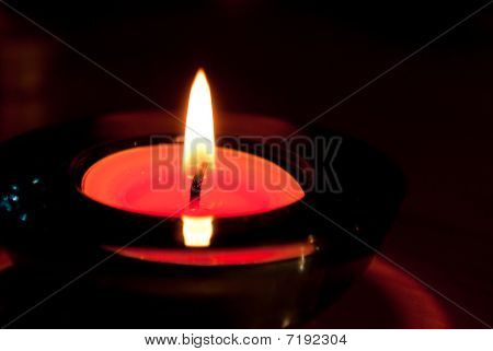 Red candle in a glass sconce.