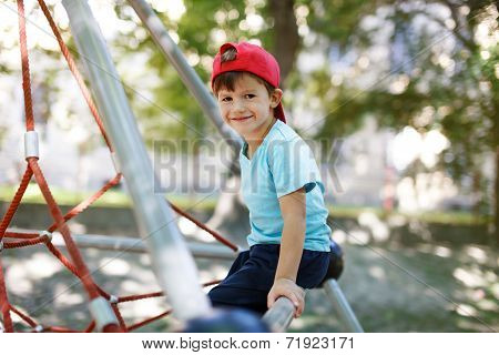 Little Boy In Cap Sit On Jungle Gym
