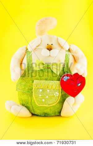 Soft Toy. The dog Dressed Coveralls With Gold Toy Heart In Its Hand