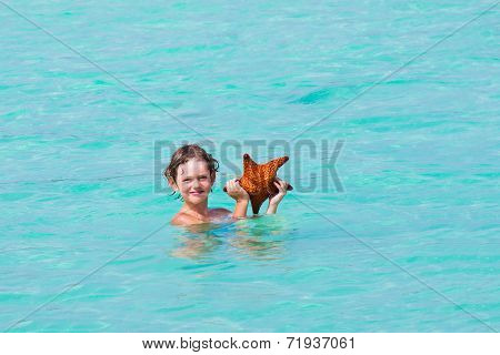 Little Boy Playing With A Star Fish