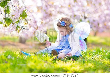 Curly Toddler Girl In Fairy Costume Playing In Fruit Garden