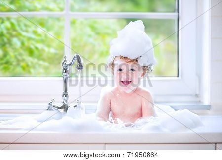 Funny Baby Girl Playing With Water And Foam In A Big Kitchen Sink