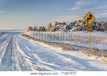 back country road over prairie at Natural Fort in northern Colorado in winter scenery, a road sign with bullet holes