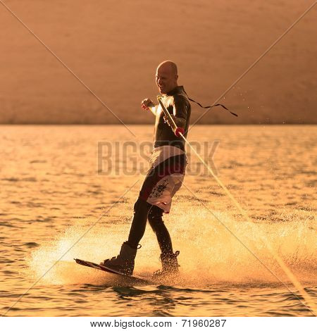 Wakeboarder in sunset.