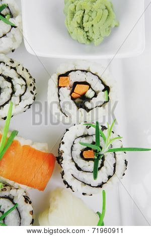 Maki Rolls and California rolls made of fresh raw Salmon, Tuna and Eel with Cream Cheese and Avocado . Isolated over white background . on long white plate . Maki Sushi and Nigiri