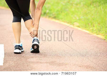 woman runner hold her injured leg
