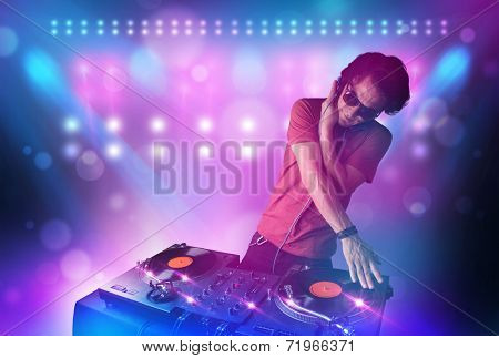 Young disc jockey mixing music on turntables on stage with lights and stroboscopes