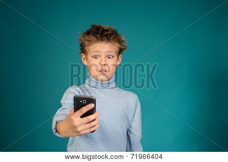 Surprised boy playing games on smartphone on blue background.
