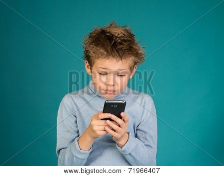 Funny boy playing games on smartphone on blue background.