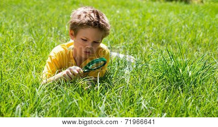 Happy boy enjoying sunny summer or autumn day in nature on green grass. Kid with magnifying glass ou