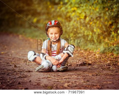 happy little girl sitting on roller skates in the forest