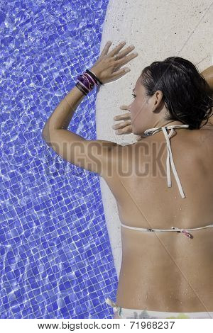 Young Woman Lying On The Edge Of A Pool