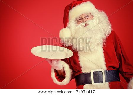 Jolly Santa Claus holds big white plate over festive red background. Copy space. Christmas treats.