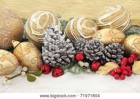 Christmas gold bauble decorations with holly and winter greenery over snow background.