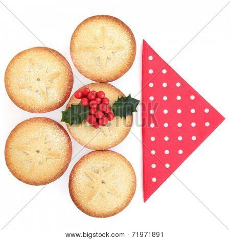 Christmas mince pie cakes and holly with red serviette over white background.