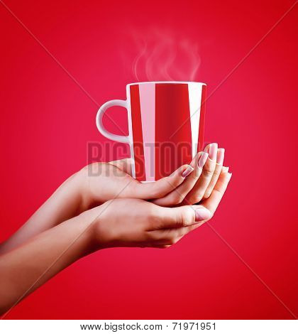 Close up on woman's hands holding red cup of hot coffee isolated on red background, tasty hot drink, time for a break