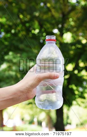Hand holds bottle with water on bright background