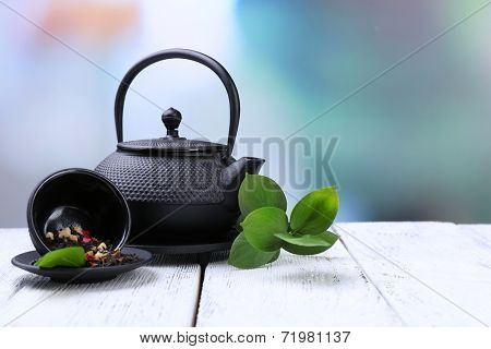 Black teapot, bowl and tea on color wooden table, on bright background