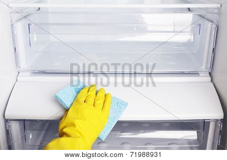 Woman's hand washing refrigerator with duster