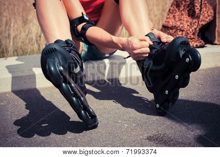 Young Woman Putting On Rollerskates
