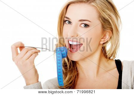 Woman on diet with tape-measure on fork