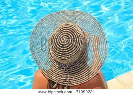 Young woman with straw hat sitting on the ledge of the pool.