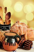 stock photo of chocolate spoon  - Jar of hot chocolate and sweet bread pan de muerto with wooden chocolate grinder and spoons on festive background - JPG