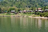 stock photo of ou  - Fishing village Muang Ngoi Neua in Laos can be only reach at Nam Ou river - JPG