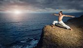 picture of virabhadrasana  - Man in white trousers doing Yoga warrior pose on the cliff near the ocean in Kerala India - JPG