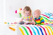 stock photo of brother sister  - Two children cute curly little toddler girl and a funny baby boy brother and sister reading a book sitting in a sunny bedroom on a wooden white bed with colorful rainbow bedding enjoying a nice weekend morning - JPG